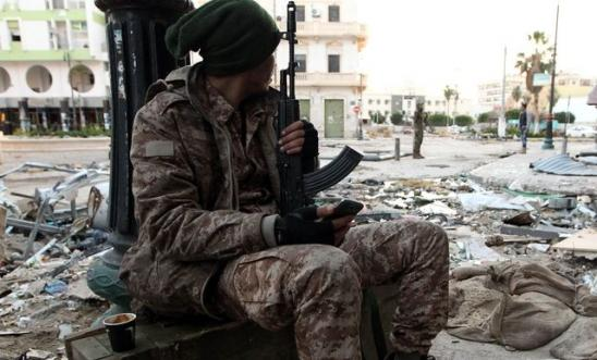 225486_a_libyan_soldier_loyal_to_libya_s_internationally_recognised_government_rests_on_the_sidewalk_of_benghazi_1
